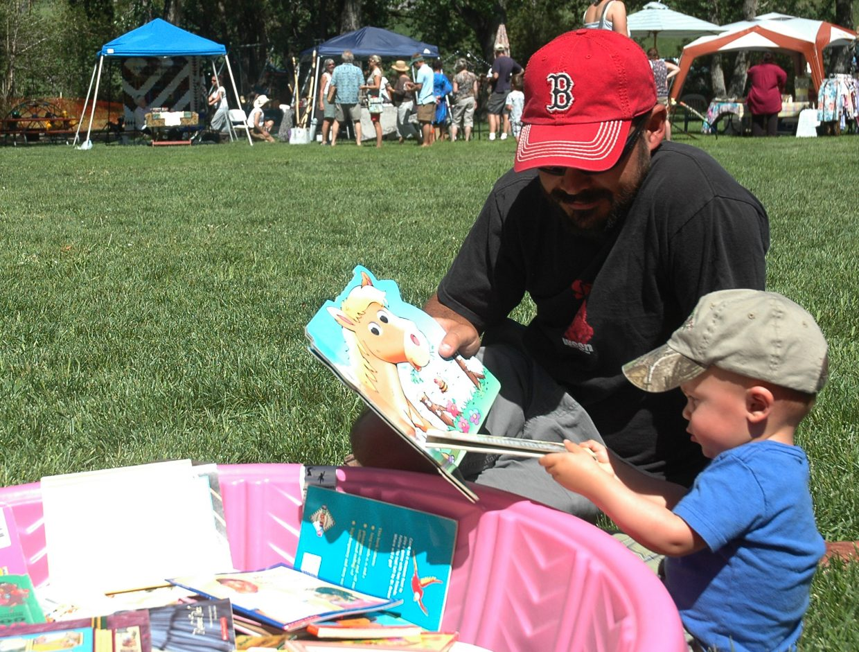 Jeremiah Arnold and his 1-year-old son Dylan look through books at the South Routt Libraries booth at the Taste of South Routt Festival Saturday in Oak Creek.