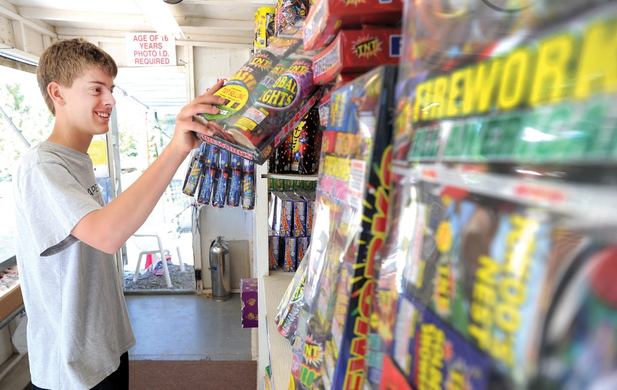 Grant Birkinbine stocks the shelves inside the TNT Fireworks stand in Steamboat Springs on Tuesday morning. Several counties and municipalities in Northwest Colorado will consider enacting Stage 1 fire restrictions next week.
