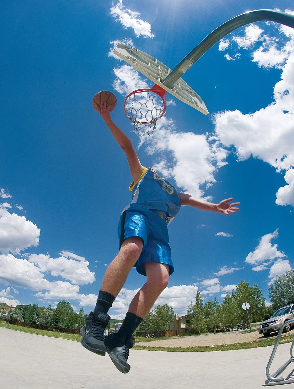 Rylan Laszewski stretches to make the shot Tuesday afternoon at a basketball court in the Steamboat II neighborhood.
