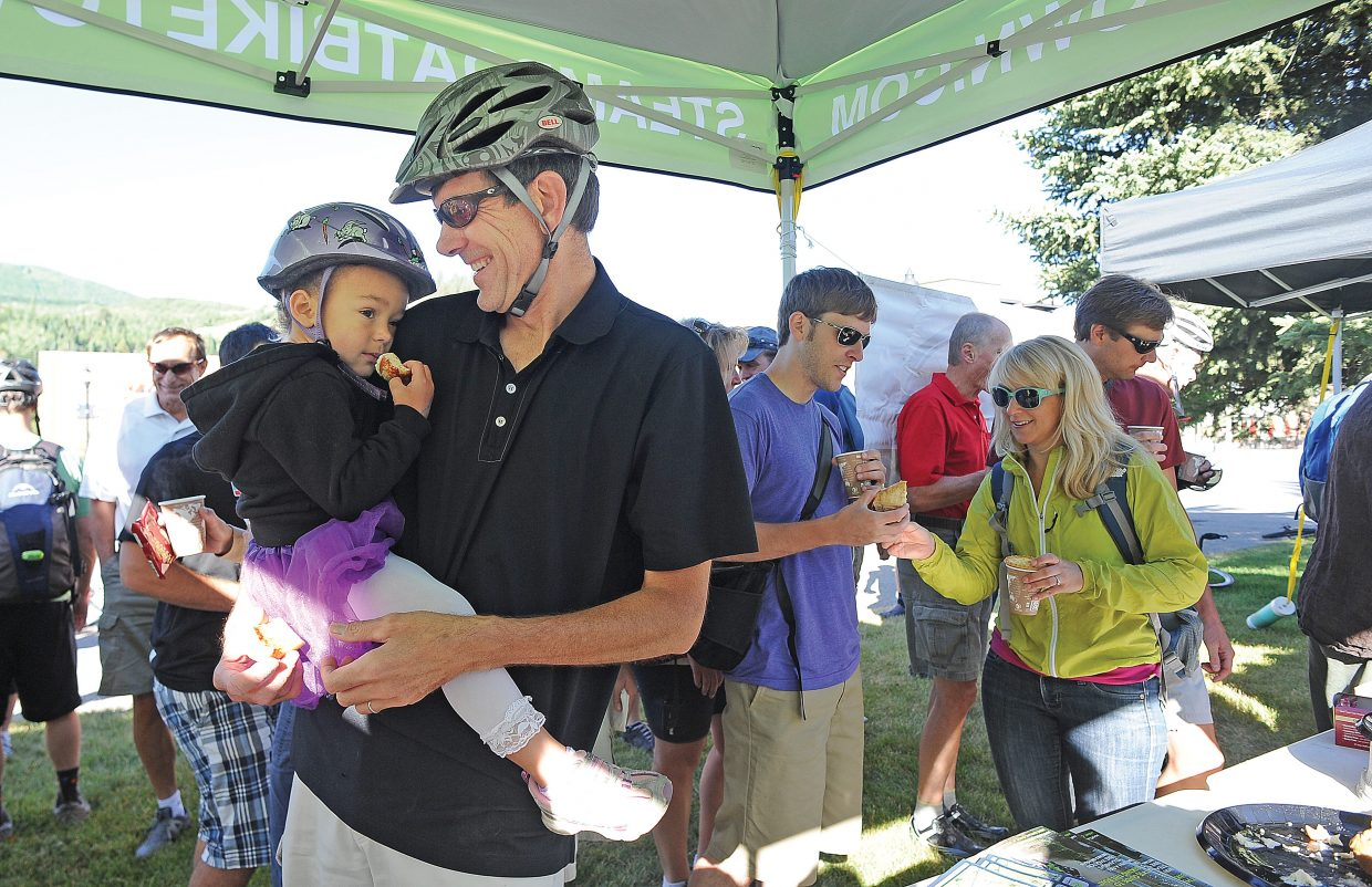 Maya Peilet enjoys breakfast with her dad, Michael, on the courthouse lawn during the Bike to Work Day breakfast.