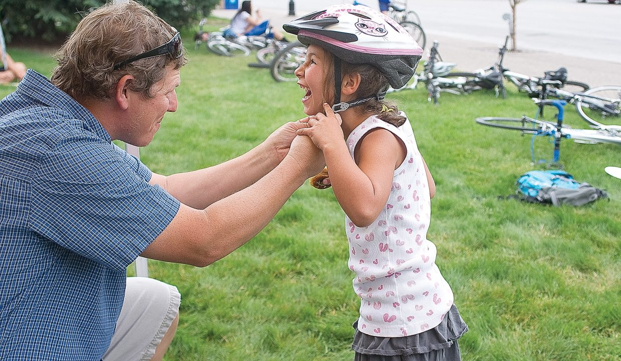 Chris Daniels adjusts his daughter Izbel's helmet during the Bike to Work Day breakfast Wednesday morning on the Routt County Courthouse lawn. The event, which was put on by Routt County Riders and Honey Stinger, offered cyclists who elected to bike to work a free breakfast.