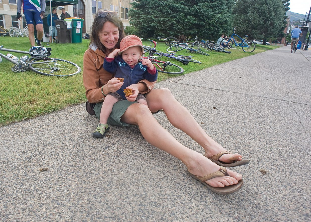 Liz Baldwin shares a muffin with her son Everett during the Bike to Work Day breakfast Wednesday morning on the Routt County Courthouse lawn. The event, which was put on by Routt County Riders and Honey Stinger, offered cyclists who elected to bike to work a free breakfast.