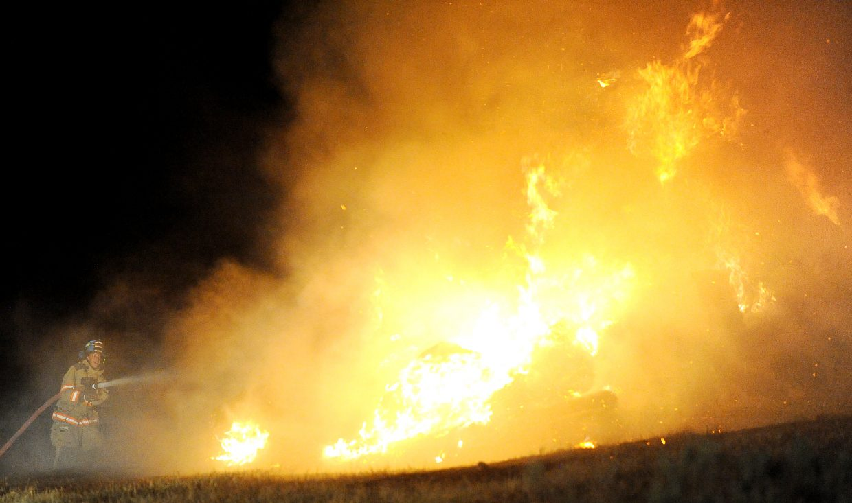 A firefighter blasts water into a burning hay stack Thursday night near Stagecoach Reservoir.