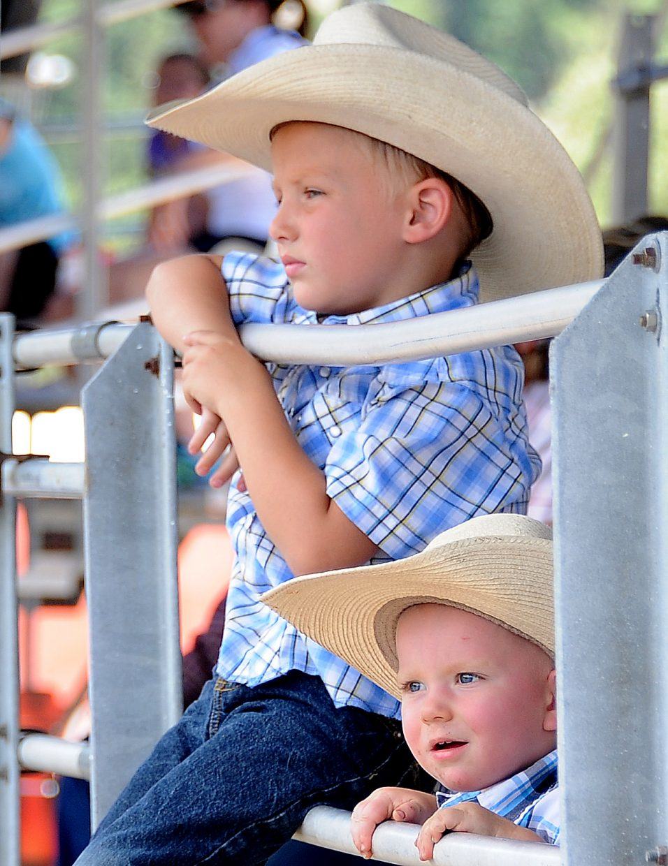 Kaden Moore, 6, left, and Riley Mahon, 1, take in the ranch rodeo in Steamboat Springs on Sunday.
