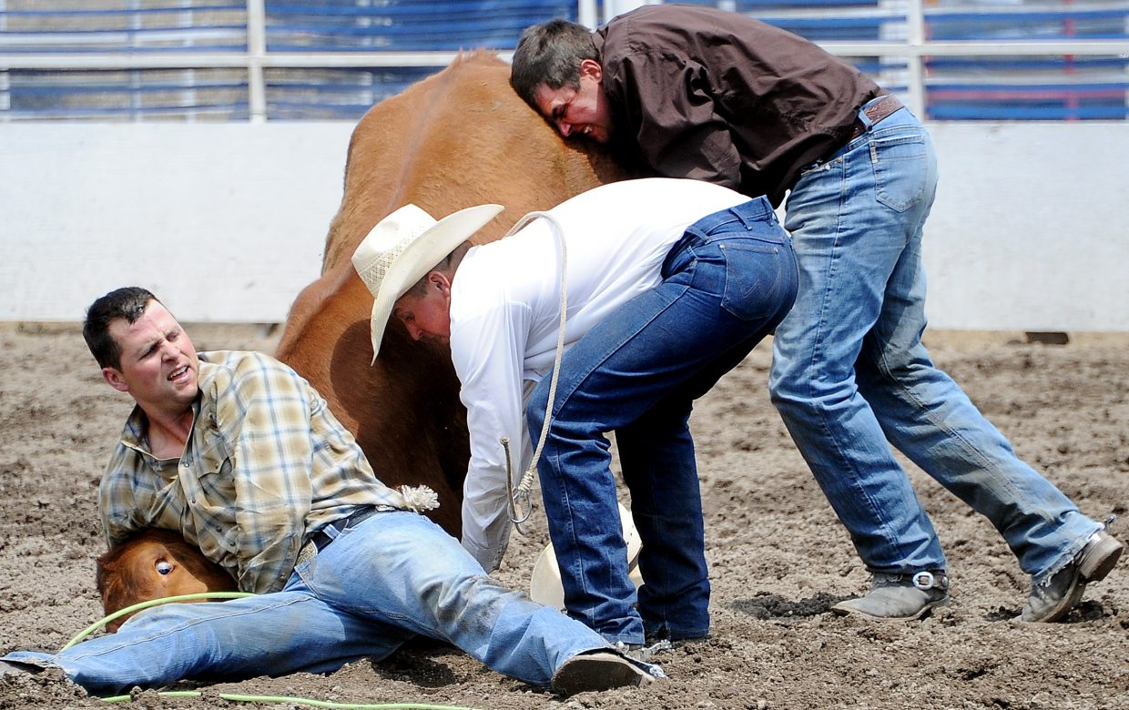 Luke Kelley, left, Shea Meeks and Ty Pryor try to tackle and tie up a steer Sunday during the ranch rodeo in Steamboat Springs.