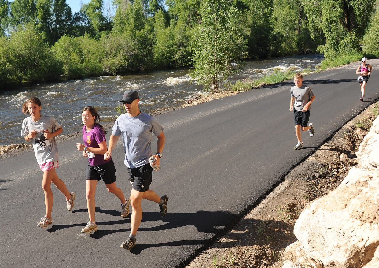Rachael Green, center, and Rodney Green, right, run with Lark Skov on Saturday during the Steamboat Springs Running Series's Mountain Madness event. The race, which drew nearly 300 runners, was a fundraiser for the Rebecca Green Foundation. Green drowned two years ago in Fish Creek.