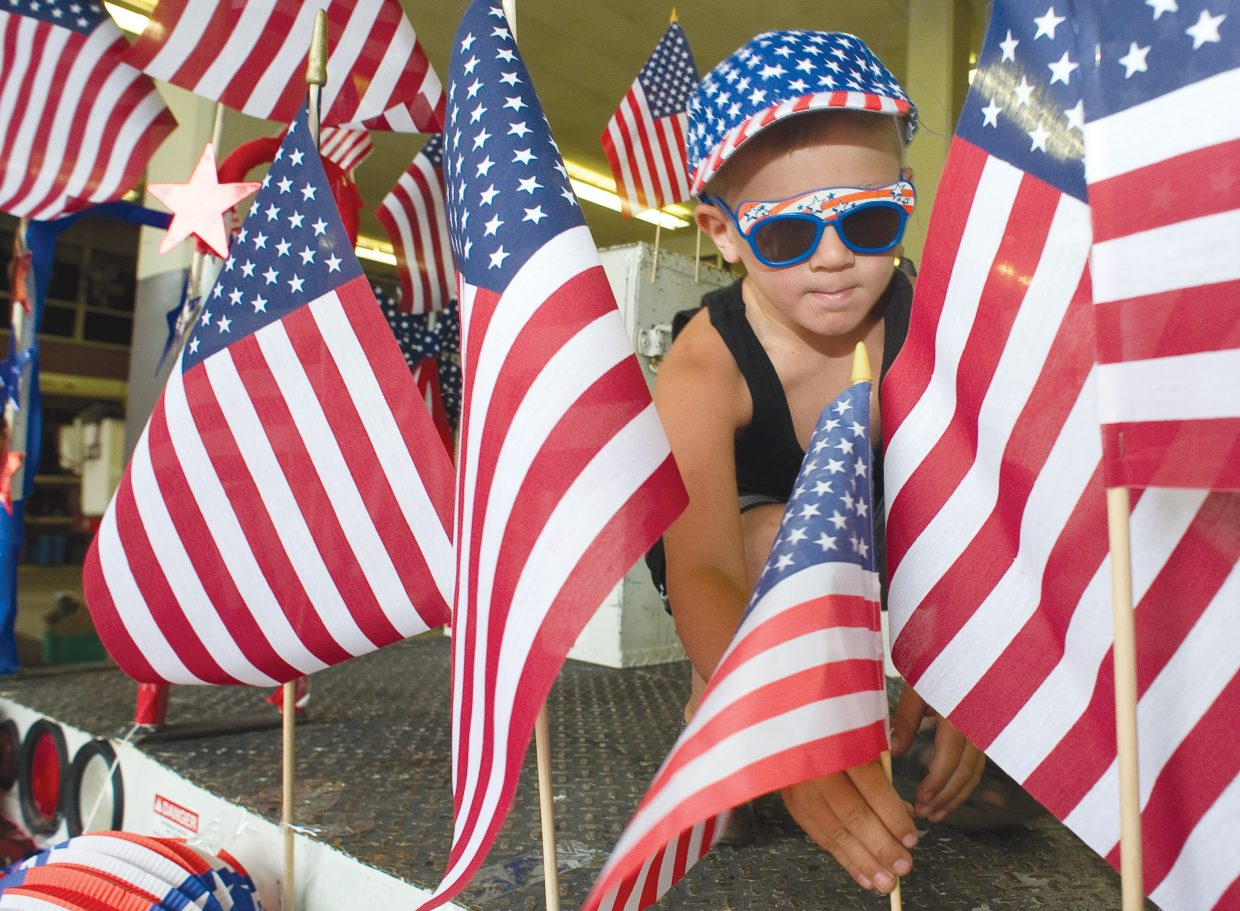 Bryan Vandenburg places a flag on the Yampa Valley Electric Association float while preparing for the Fourth of July parade in Steamboat Springs in 2013.