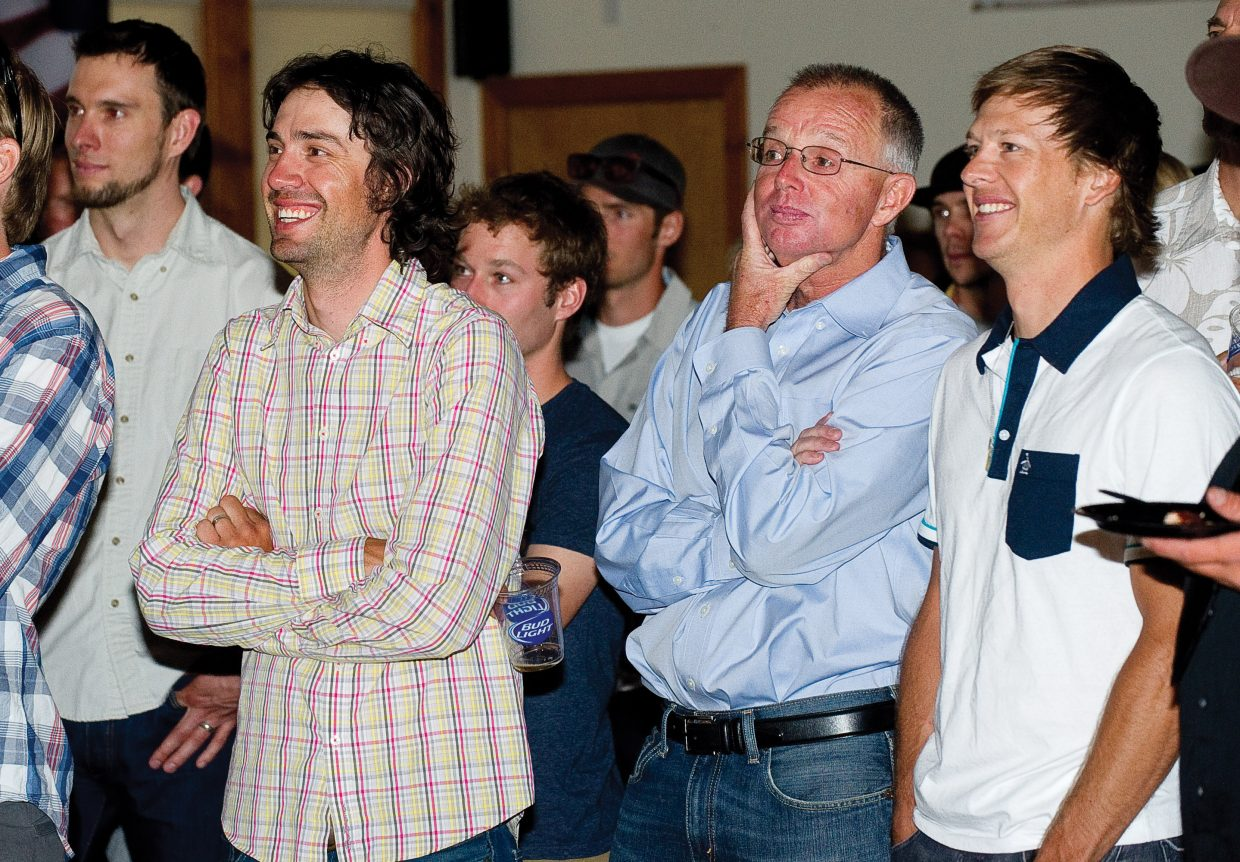 World champion and three-time Olympic silver medalist Johnny Spillane, from left, laughs Wednesday evening alongside former coach Tom Steitz and former teammate Todd Lodwick while watching a slideshow highlighting his career. Spillane retired from the U.S. Nordic Combined Ski Team earlier this year and was recognized by coaches, teammates, family and friends during a party Wednesday evening at Olympian Hall.
