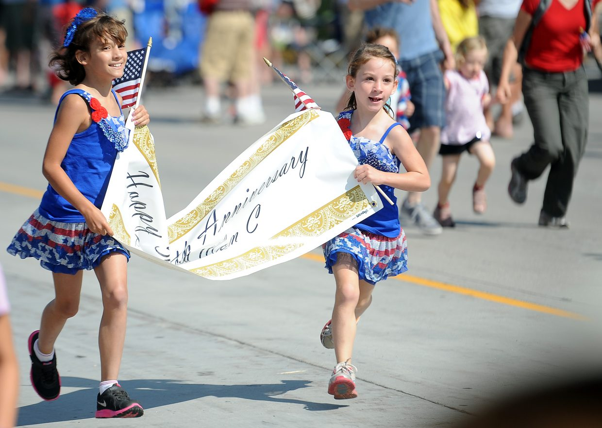 Peyton Tinsley, 9, and Kate Clark, 6, near the end of the Steamboat Sprint. They ran with a banner celebrating their grandparents Guy and Linda Clark's 50th anniversary.