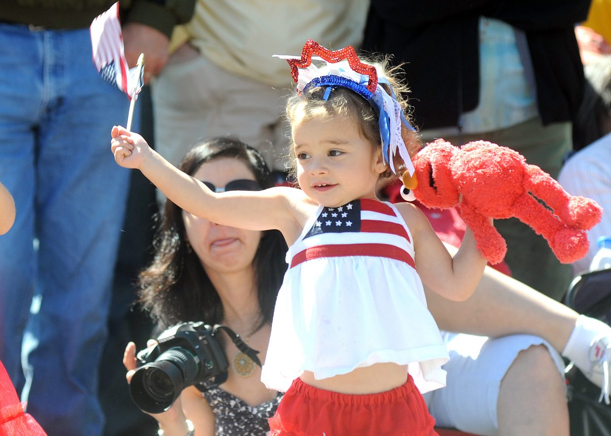 Caroline Wideman waves a flag and waits for the next float Sunday during the Fourth of July parade in downtown Steamboat Springs.