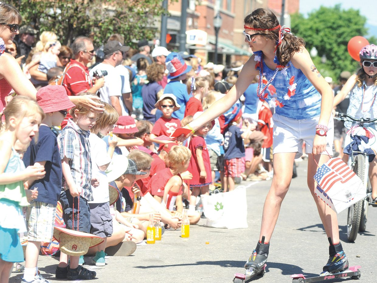 Steamboat Springs Winter Sports Club athlete Lucy Newman hands out candy while roller-skiing down Lincoln Avenue during a Fourth of July parade in downtown Steamboat Springs.