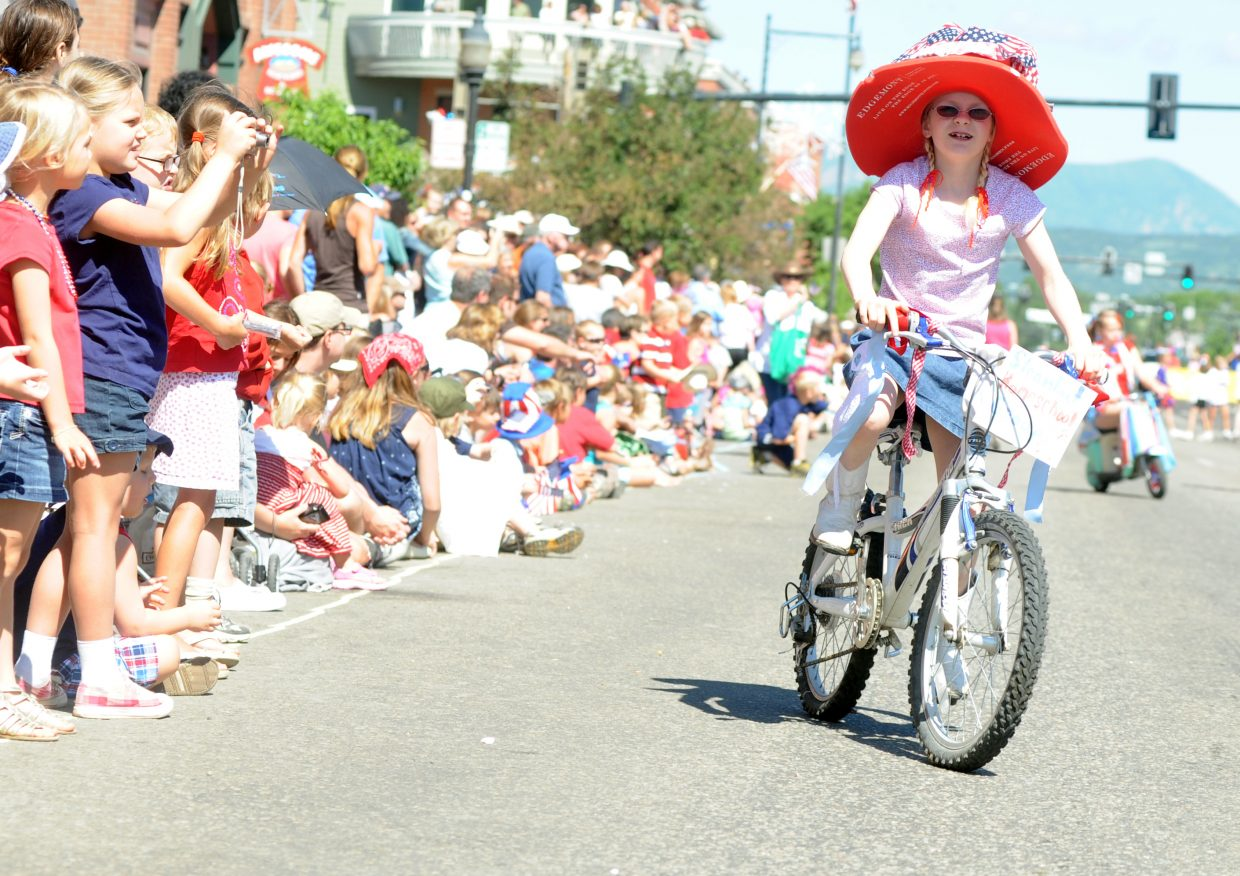 Amie Cook, 8, rides her bike during the Fourth of July parade in downtown Steamboat Springs.