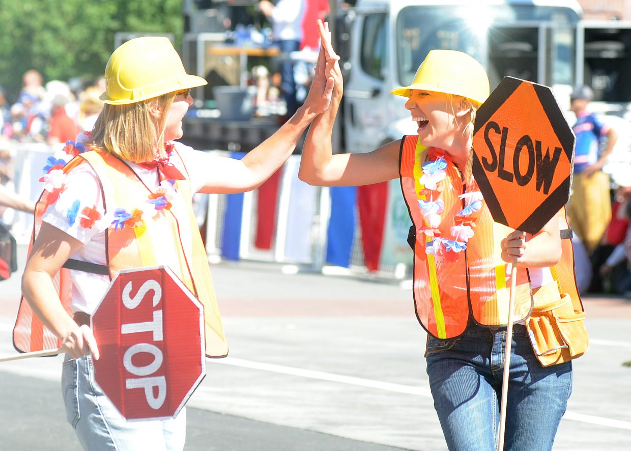 Debbie Born, right, high fives a co-worker Sunday during the parade after the pair participated in a dance as a part of the Yampa Valley Bank.