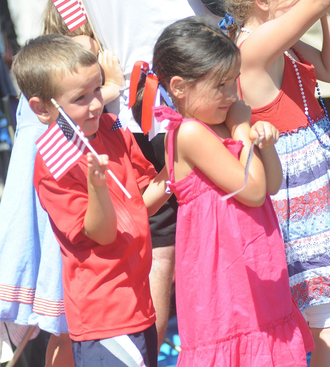 Brett McGraw hides behind his cousin Avery McGraw as the crowd is sprayed on Sunday during the Fourth of July parade in downtown Steamboat Springs.