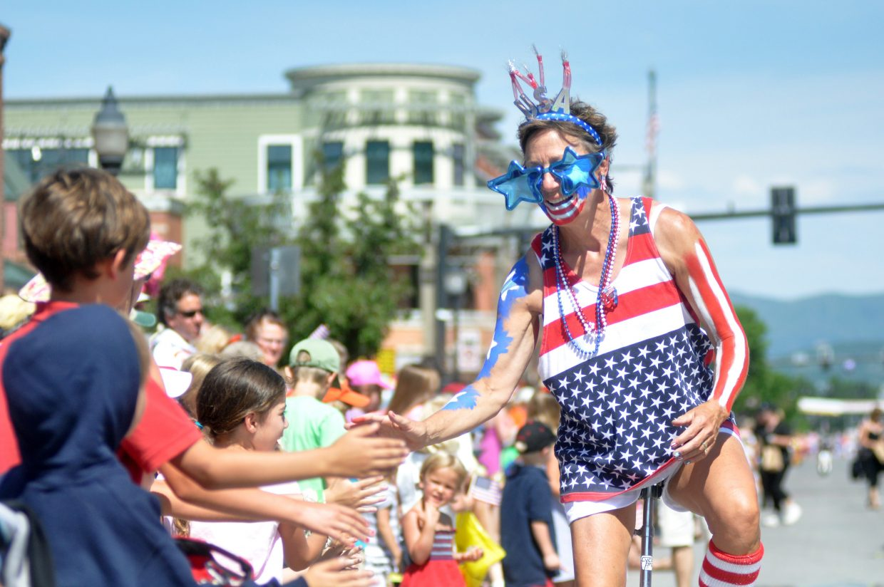Stacey Gibbons high-fives spectators Monday as she rides a unicycle down Lincoln Avenue during Steamboat Springs' Fourth of July Parade. Thouands of spectators packed the downtown area for the parade, which was followed by other Independence day festivities including ski jumping at Howelsen Hill and a block party at Tread of Pioneers Museum.