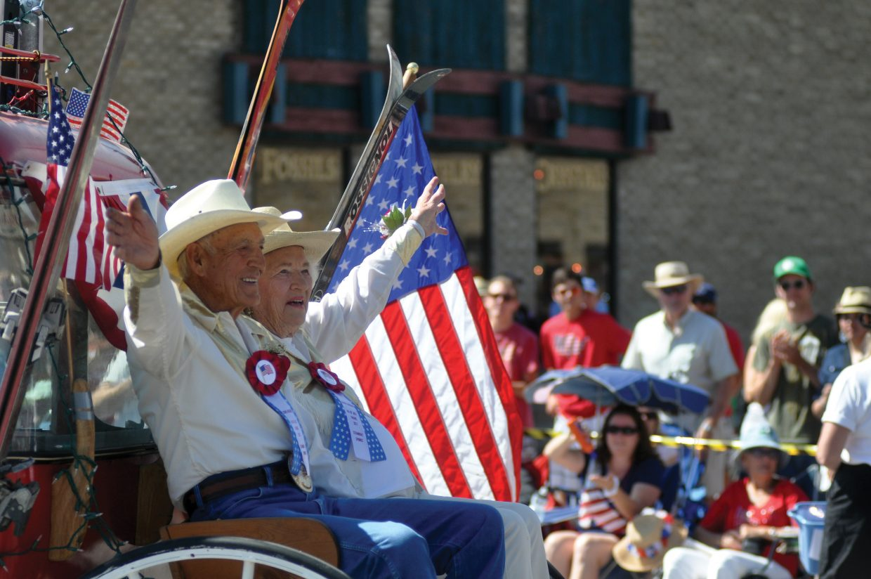 Parade grand marshals Angelo and Helen Iacovetta wave from the back of a stagecoach Monday during Monday's Fourth of July parade in Steamboat Springs.