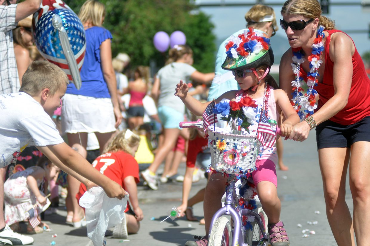 Ella Piret, 6, throws candy to spectators Monday on Lincoln Avenue during Steamboat's Fourth of July parade. Classic cars, horses, and floats made their way through the downtown area during the festivities.