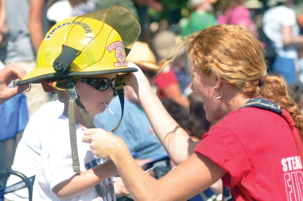 Steamboat Springs Fire Rescue recruit Lisa Nelson helps Henry Hinkle try on a firefighter's helmet during Steamboat's Fourth of July parade.