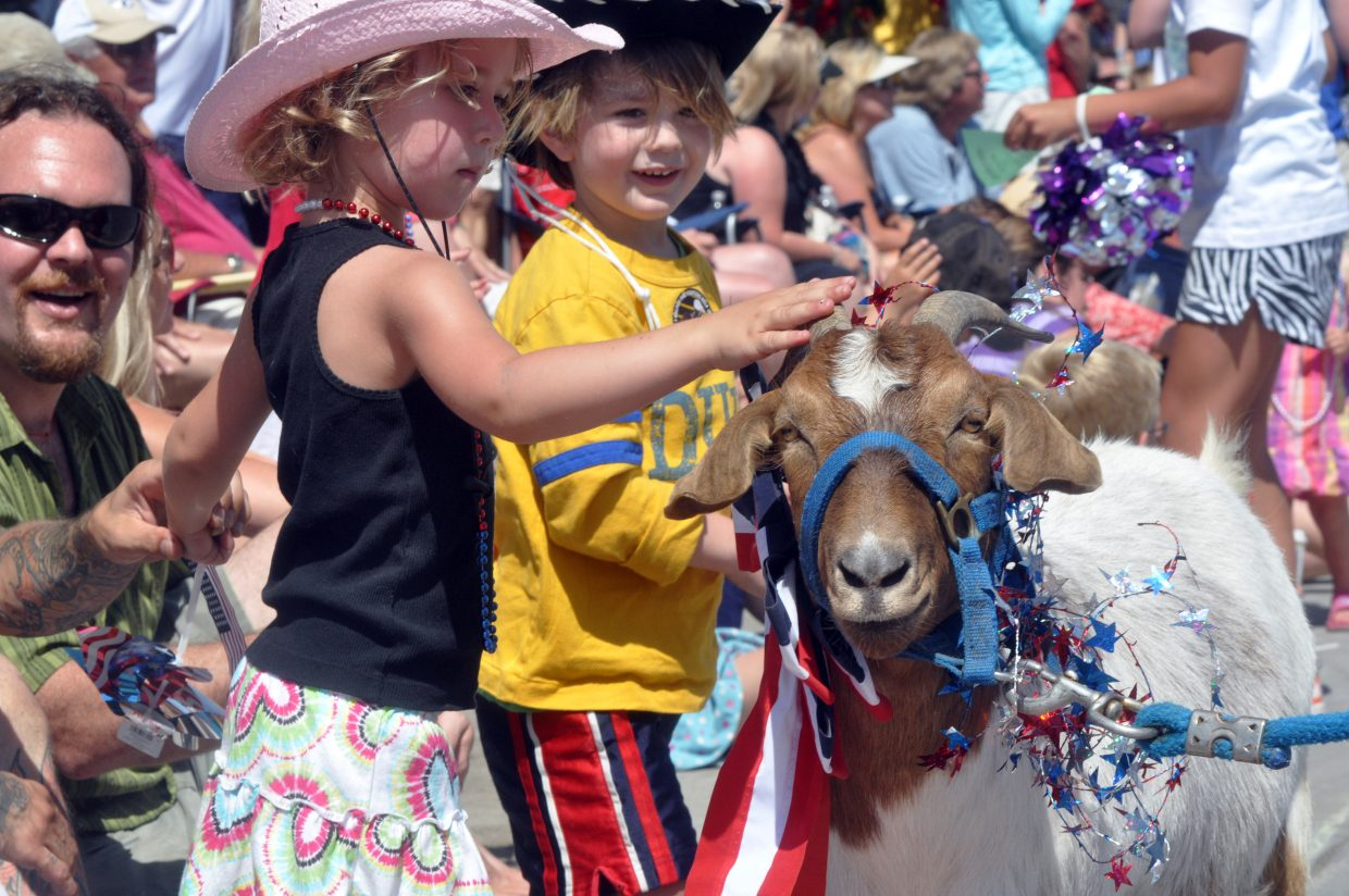 Addi Lustick pets Flower the goat Monday during Steamboat's Fourth of July parade.