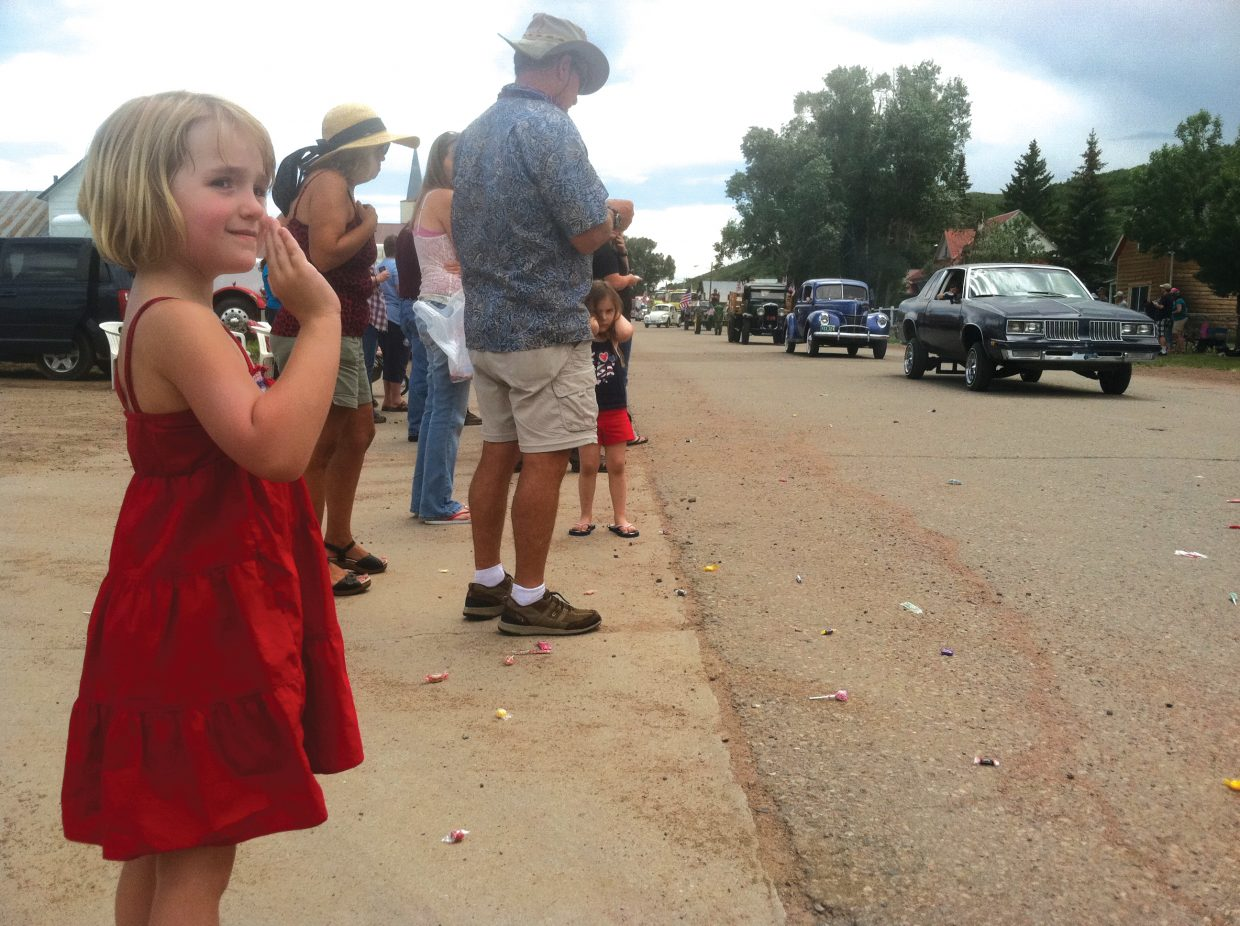 Caroline James, 5, of Loveland, waves to cars during Yampa's annual Fourth of July parade. Caroline was visiting relatives this weekend in the South Routt town.