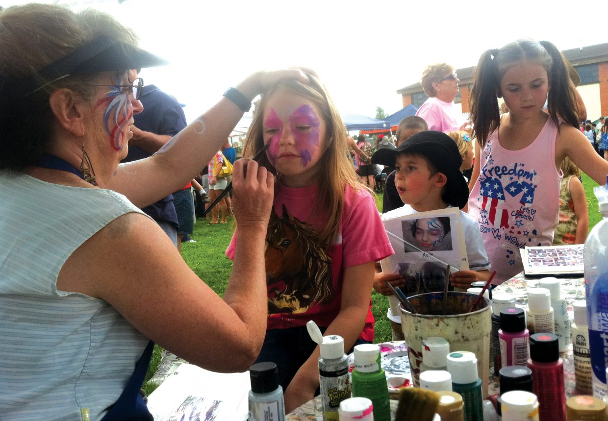 Suzy Pattillo paints a butterfly on the face of Jade Boline, 7, of Colorado Springs. Pattillo has operated Miss Suzy's Face Painting during the Yampa Fourth of July picnic for 12 years.