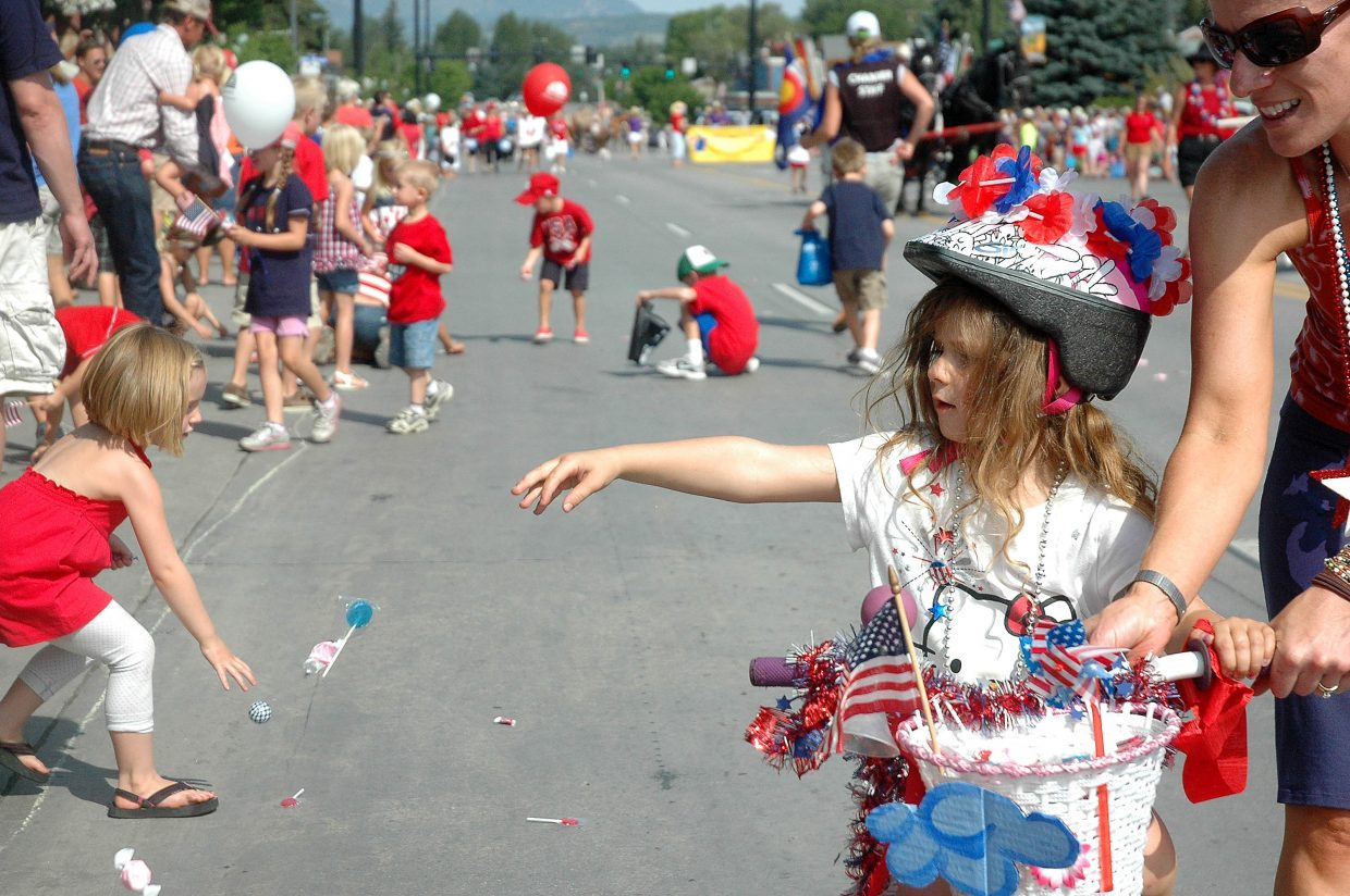 Gracie Piret, 3, of Steamboat, hands out candy from her bicycle during Wednesday's Fourth of July Parade in downtown Steamboat Springs. Sixty floats rolled down Lincoln Avenue during the annual celebration.