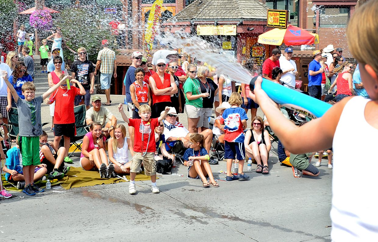 Hannah Murphy, 9, unloads a tank full of water on eager parade watchers during the Fourth of July parade in downtown Steamboat Springs. Murphy and her friends and family, on the Hog Island Boats float, were popular on the hot July morning, parade-goers eager for a cool down.
