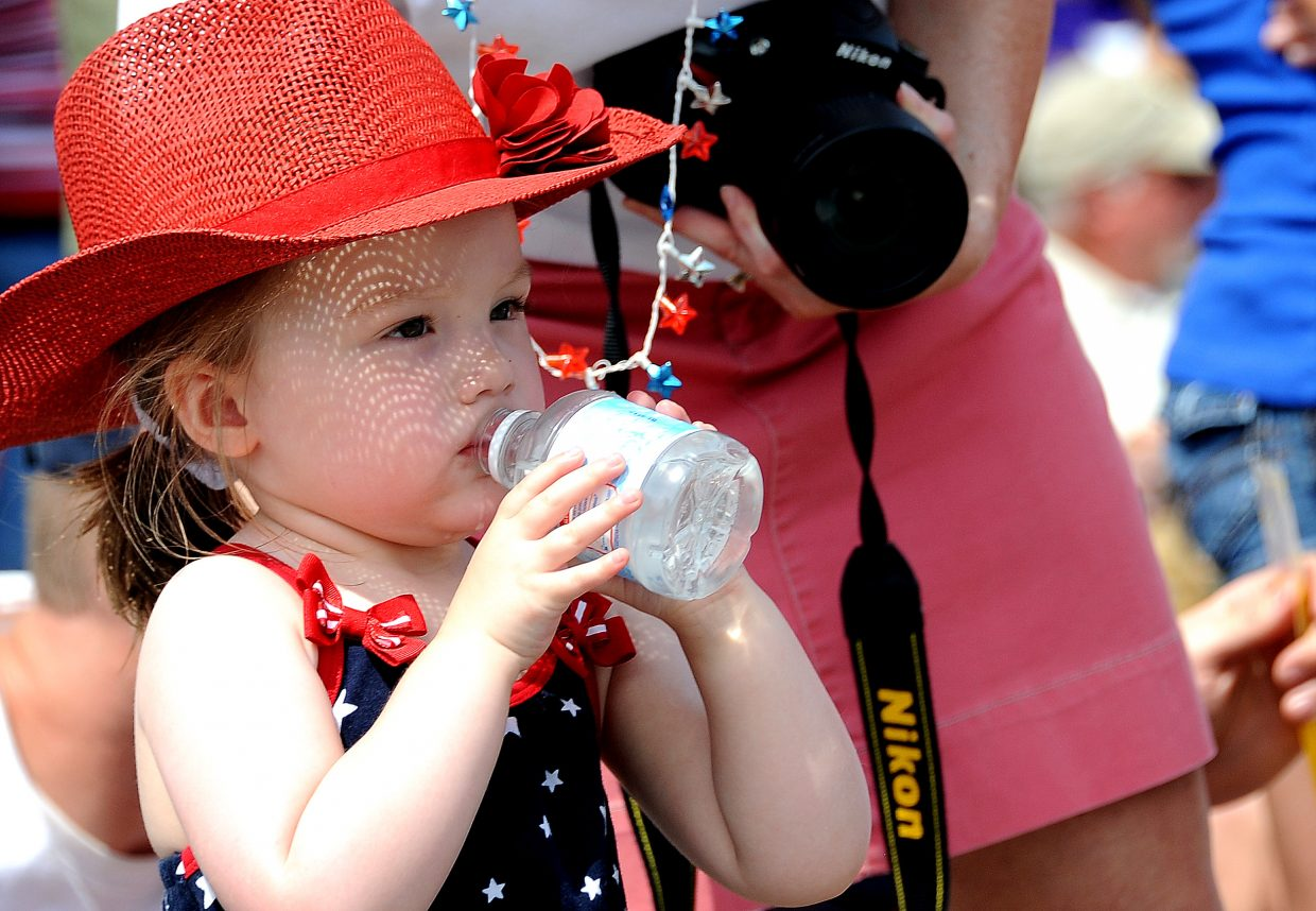 Emma Price, 2, downs some water to try to cool down during Wednesday's Fourth of July parade in downtown Steamboat Springs.
