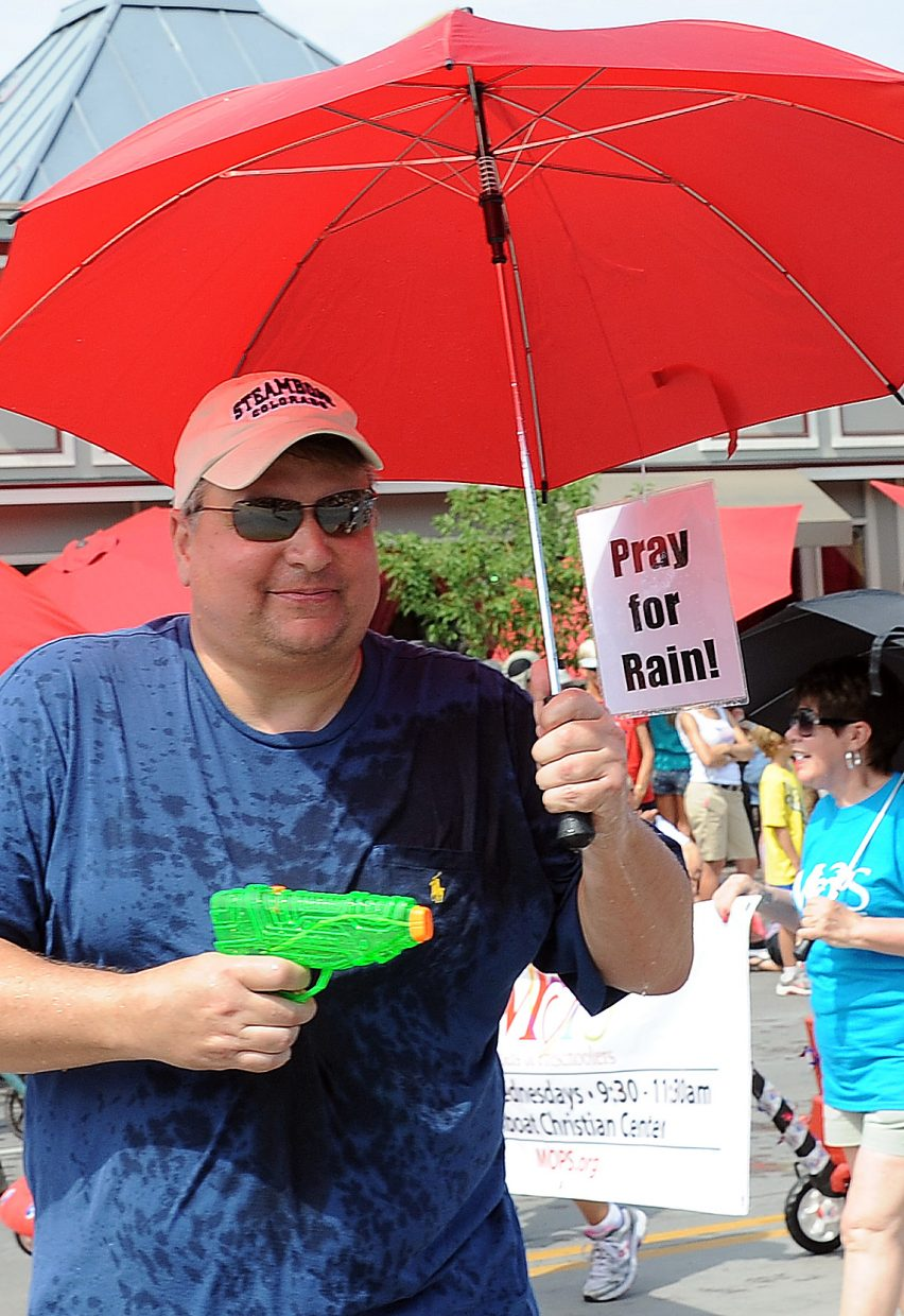 """Ready with a watergun, an umbrella and a """"Pray for rain"""" sign, Todd Moser makes his way down Lincoln Avenue during the Fourth of July parade on Wednesday."""