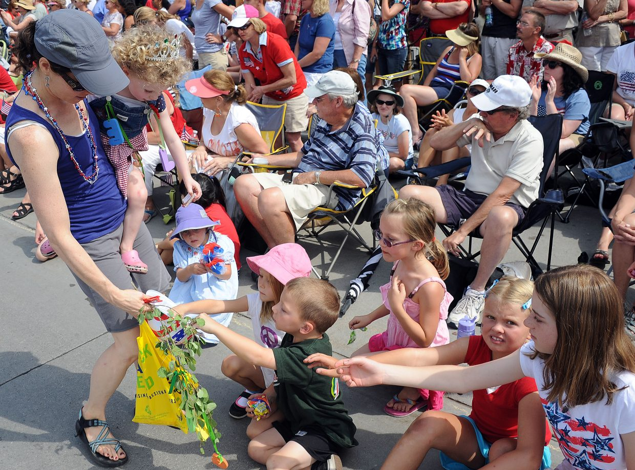 Nicole Wobus and Elise, 3, hand out candy during the Fourth of July parade Wednesday in downtown Steamboat Springs.