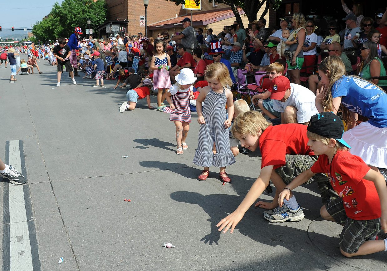 Children break after candy thrown onto the street Wednesday during the Fourth of July parade in downtown Steamboat Springs.