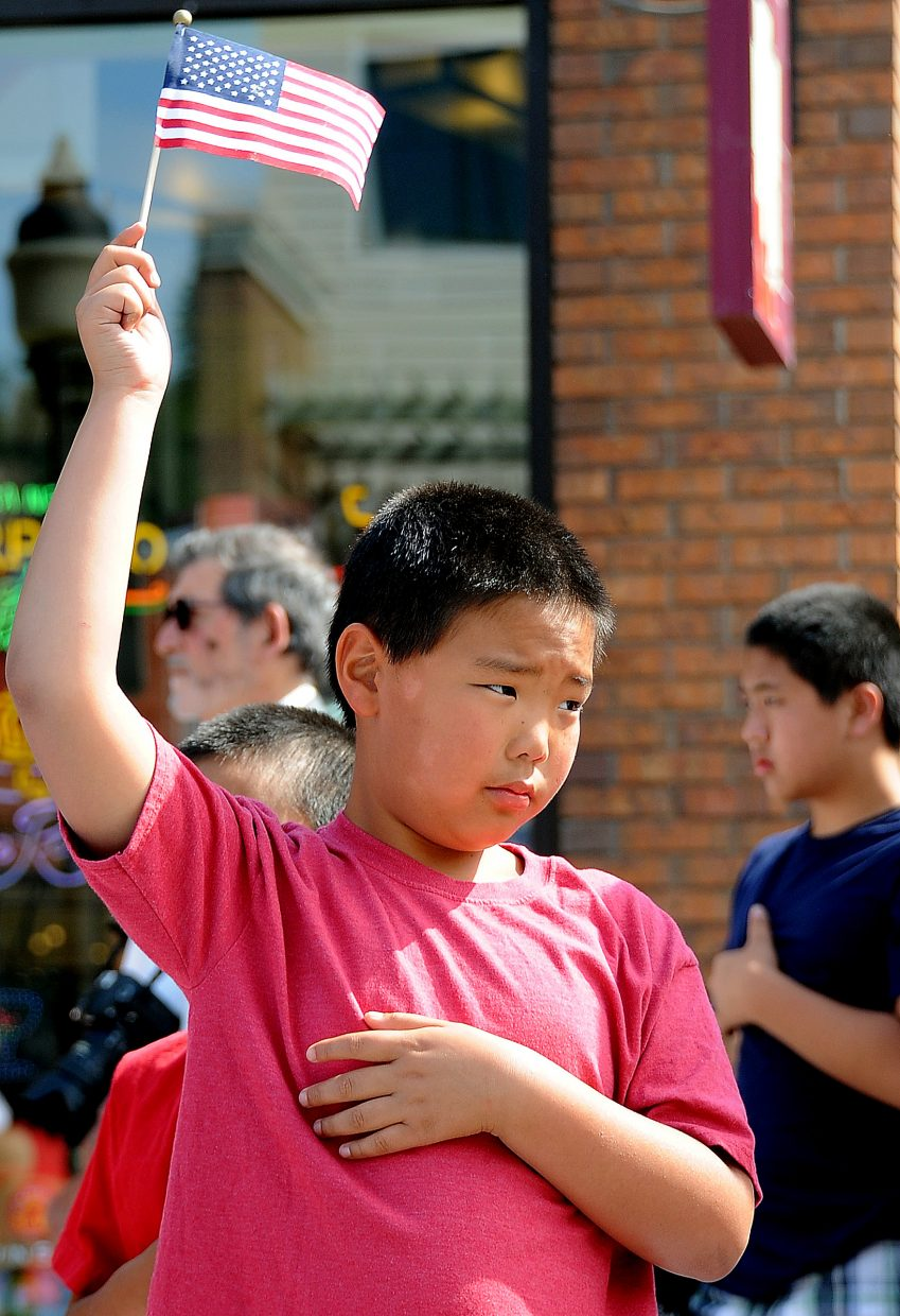Colin Knoll, 9, stands with his flag held high and his hand over his heart Wednesday before the Fourth of July parade in downtown Steamboat Springs.