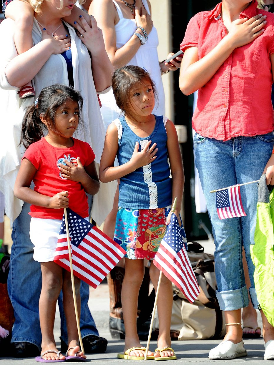 Addie, 5, left, and Ava Chester listen to the national anthem Wednesday before the Fourth of July parade in downtown Steamboat Springs.