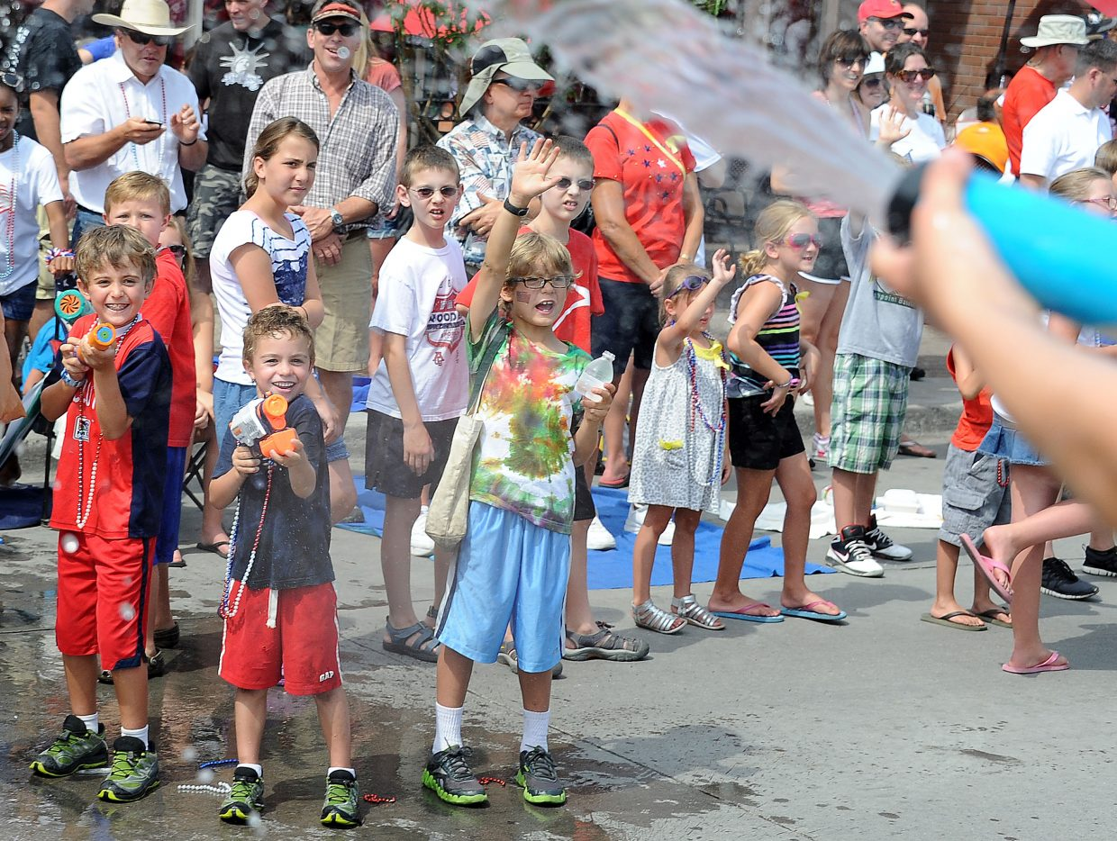 Road-side water gunners take aim at a float filled with children armed with water guns Wednesday during the Fourth of July Parade in Steamboat Springs.