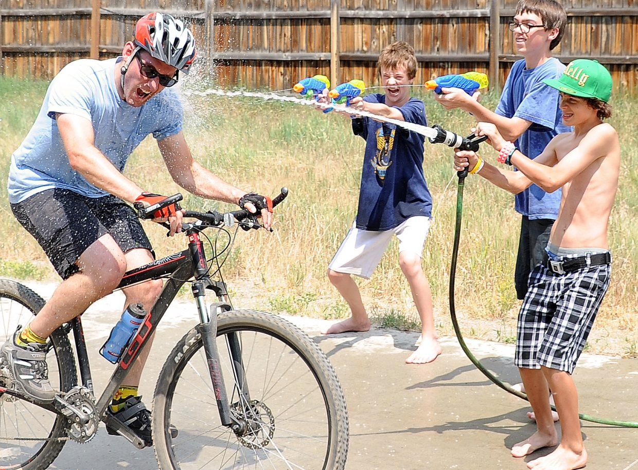 """Erik Summers, 12, left, Logan Sully, 14 and Kelly Ryan, 13 blast a rider with water Wednesday on the Yampa River Core Trail in Steamboat Springs. They were joined in the effort by Sarah Kite, 14. The event has become an Independence Day tradition for the friends, though it has evolved. A few angry riders last year taught them to hollar out """"Do you want to be sprayed?"""" as riders approached. They also had to do away with fireworks this year as the region is under a fire ban."""