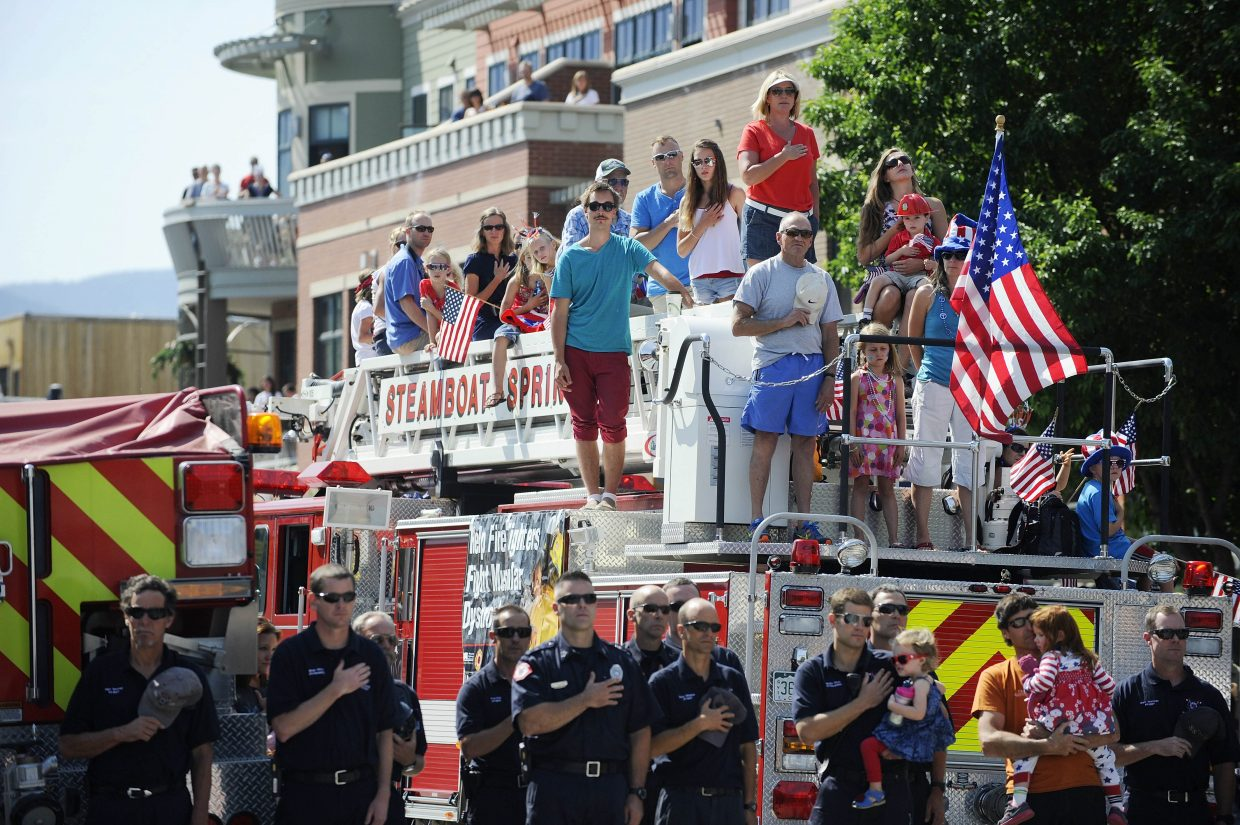 Parade participants listen to the national anthem during the July 4 parade on Lincoln Avenue.