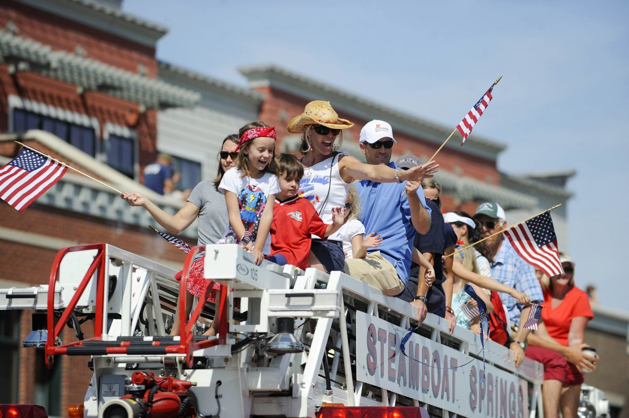 Parade participants wave at spectators from a Steamboat Springs Fire Rescue ladder truck during the July 4 parade on Lincoln Avenue.