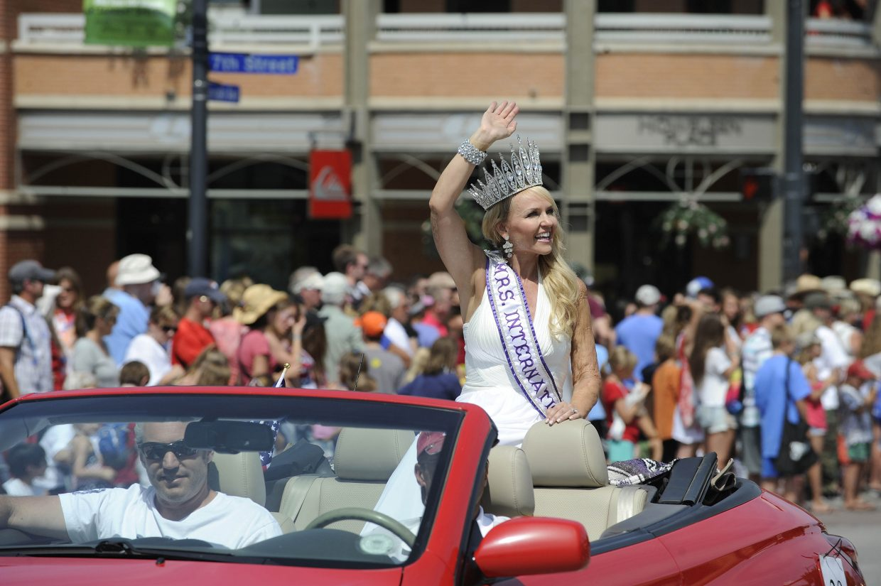 Mrs. International 2012 Sarah Bazey makes one of the last two public appearances of her reign perched on the back of a convertible as it rolls down Lincoln Avenue during the July 4 parade.
