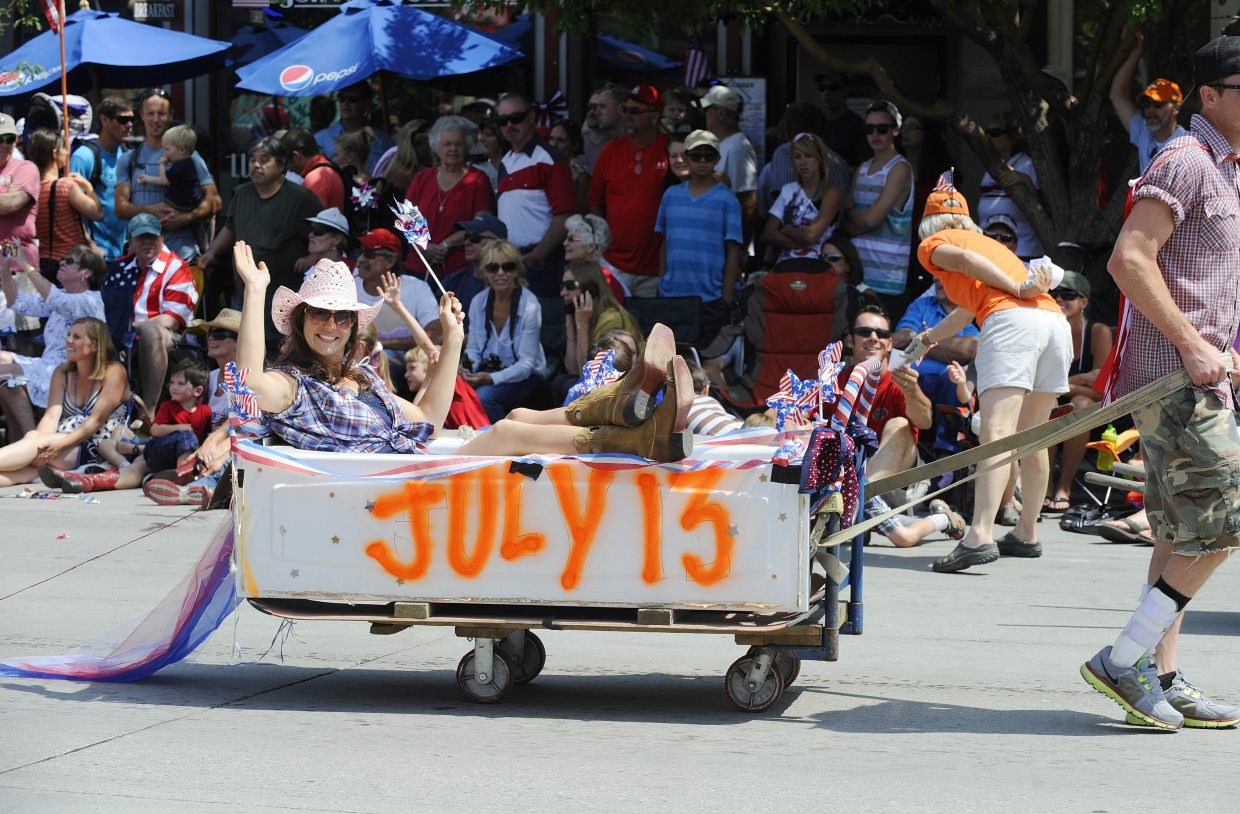 Veanna Mathey rides in a bathtub to help promote the July 13 Redneck Olympics event during the July parade on Lincoln Avenue.