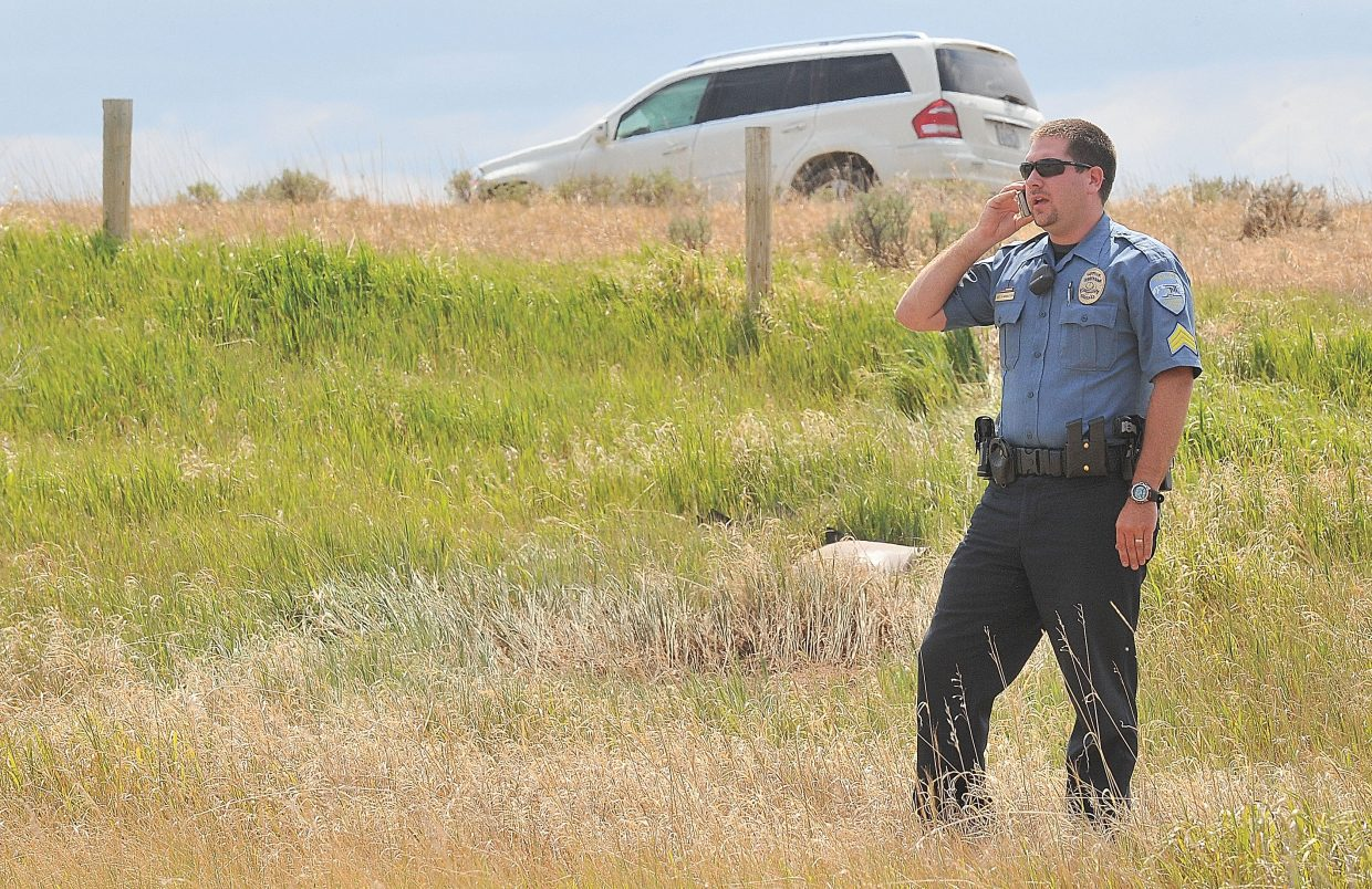 Steamboat Springs Police Sgt. Scott Middleton talks on his cellphone while investigating a crash on a private driveway located just off Routt County Road 33 on Thursday afternoon in Steamboat Springs