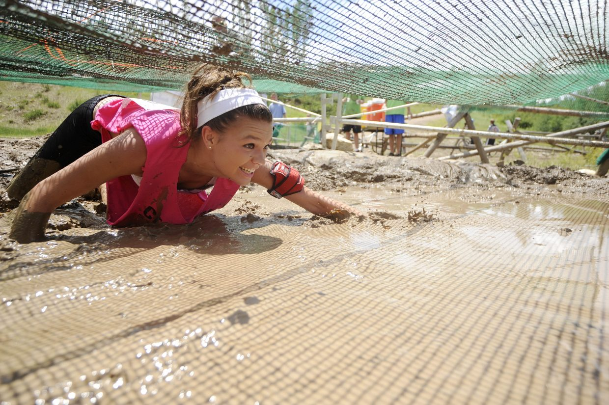 Megan Stabile crawls through the mud pit during the Steamboat Mad Mud Run on Saturday at Steamboat Ski Area.
