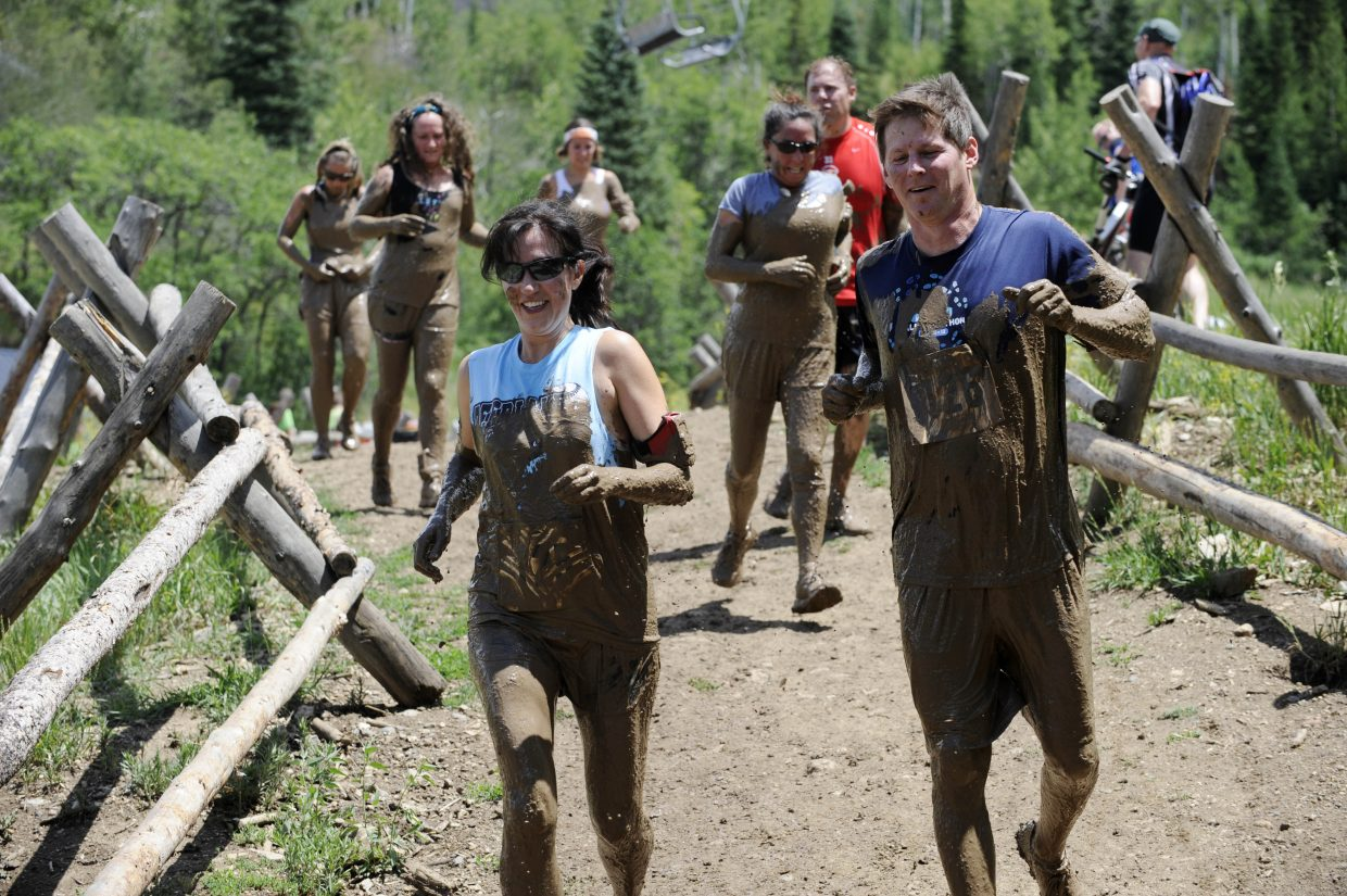 Participants run downhill after going through the mud pit during the Steamboat Mad Mud Run on Saturday at Steamboat Ski Area.