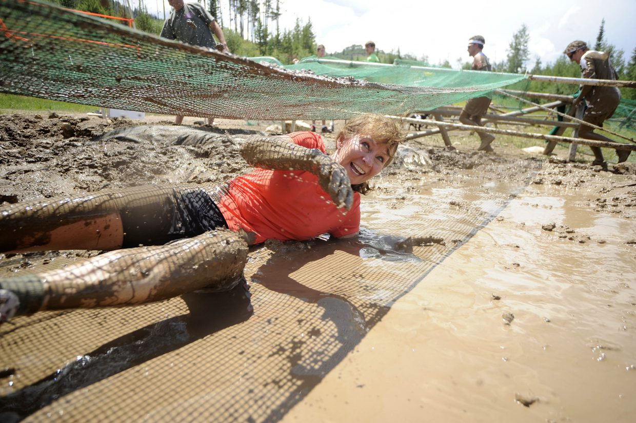 Debbie Aragon rolls through the mud pit during the Steamboat Mad Mud Run on Saturday at Steamboat Ski Area.
