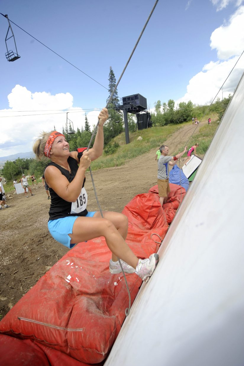 Michelle Geib attempts to climb the wall obstacle during the Steamboat Mad Mud Run on Saturday at Steamboat Ski Area.