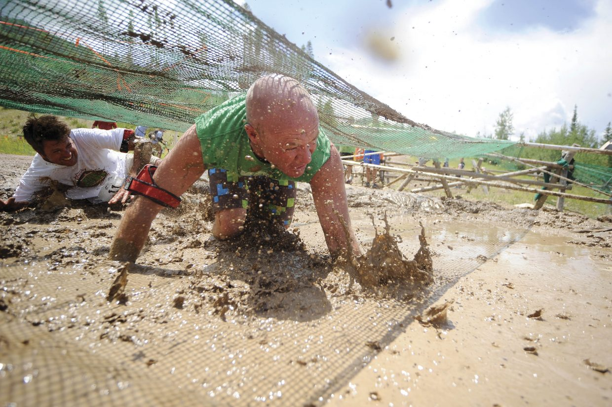 David Poussard crawls through the mud pit during the Steamboat Mad Mud Run on Saturday at Steamboat Ski Area.