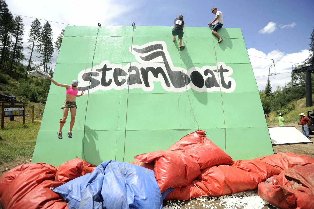 Amanda Harclerode jumps to the ground after climbing the wall during the Steamboat Mad Mud Run on Saturday at Steamboat Ski Area.