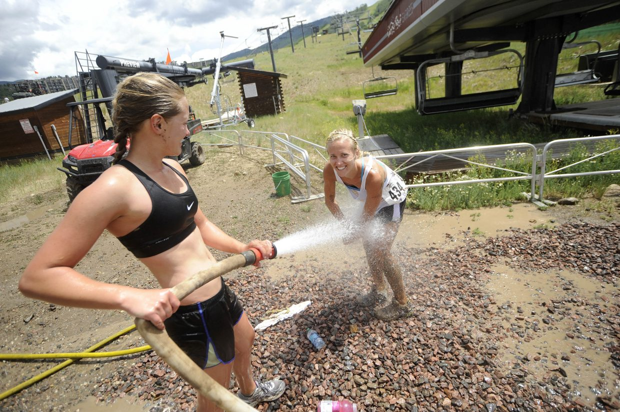Maddie Ruppel hoses off her sister Lexie Ruppel after the Steamboat Mad Mud Run on Saturday at Steamboat Ski Area.