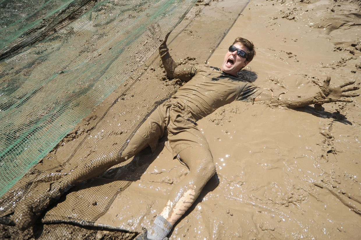 A participant goes through the mud pit during the Steamboat Mad Mud Run on Saturday at Steamboat Ski Area.
