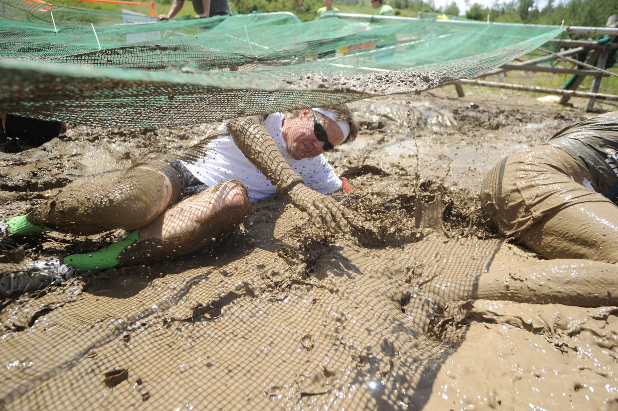 Rex Brice rolls through the mud pit during the Steamboat Mad Mud Run on Saturday at Steamboat Ski Area.