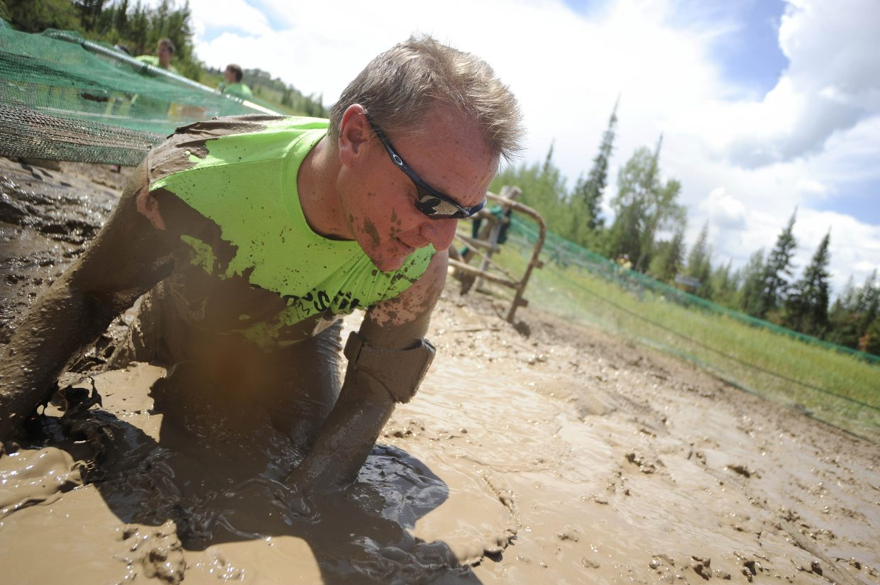 Jerry Stabile rolls through the mud pit during the Steamboat Mad Mud Run on Saturday at Steamboat Ski Area.